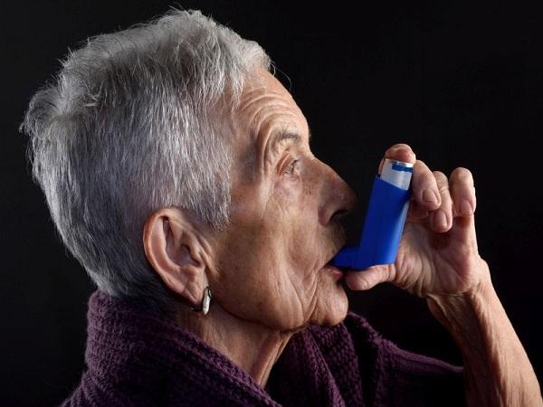 خانمی در حال مصرف اسپری استنشاقی آسم